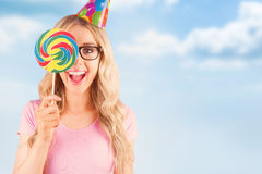 Composite image of portrait of a hipster hiding herself behind a lollipop Royalty Free Stock Photography