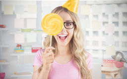 Composite image of portrait of a hipster hiding herself behind a lollipop Royalty Free Stock Image