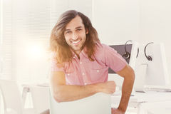 Composite image of portrait of hipster smiling while sitting on chair Stock Image