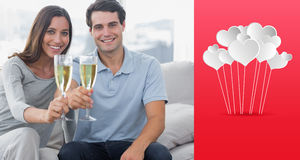 Composite image of portrait of lovers toasting their flutes of champagne. Portrait of lovers toasting their flutes of champagne against hearts Royalty Free Stock Images