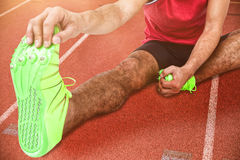 Composite image of portrait of male athlete doing stretching exercise. Portrait of male athlete doing stretching exercise against focus of sport material on race Stock Photo