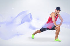 Composite image of portrait of male athlete doing stretching exercise. Portrait of male athlete doing stretching exercise against grey background Royalty Free Stock Image