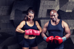 Composite image of portrait of male and female boxers with gloves. Portrait of male and female boxers with gloves against dark room Royalty Free Stock Photos