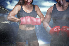 Composite image of portrait of male and female boxers with gloves. Portrait of male and female boxers with gloves against splashing of yellow color powder Royalty Free Stock Images