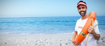Composite image of portrait of male lifeguard holding life belt Stock Photos
