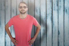 Composite image of portrait of male model wearing sunglasses. Portrait of male model wearing sunglasses against wood background Stock Photography