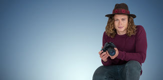 Composite image of portrait of male photographer holding camera while crouching. Portrait of male photographer holding camera while crouching against purple Stock Photography