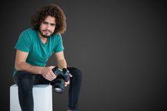 Composite image of portrait of male photographer holding camera while sitting on seat. Portrait of male photographer holding camera while sitting on seat against Royalty Free Stock Image