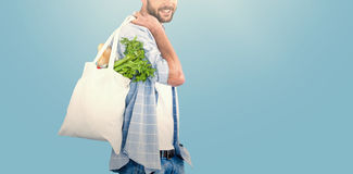 Composite image of portrait of man carrying vegetables in shopping bag Stock Photo