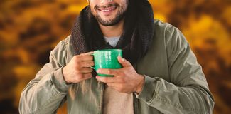 Composite image of portrait of man holding mug of coffee. Portrait of man holding mug of coffee  against autumnal ferns Royalty Free Stock Photos