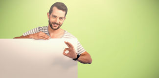 Composite image of portrait of man showing ok sign while holding blank cardboard. Portrait of man showing ok sign while holding blank cardboard against green Stock Photo