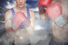 Composite image of portrait of man and woman wearing boxing gloves Royalty Free Stock Photo
