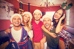 Composite image of portrait of men wearing christmas wearing giving women piggyback rides Royalty Free Stock Photo