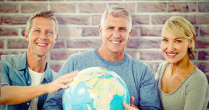 Composite image of portrait of people holding globe Stock Photos