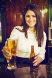 Composite image of portrait of pretty bartender serving beer at bar counter Royalty Free Stock Images
