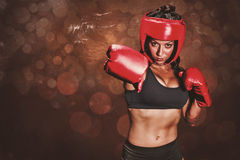 Composite image of portrait of pretty boxer with fighting stance. Portrait of pretty boxer with fighting stance against dark background stock image