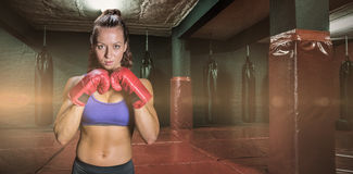 Composite image of portrait of pretty woman with fighting stance Stock Photos
