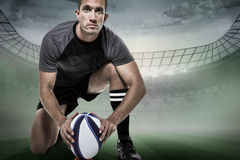 Composite image of portrait of rugby player in black jersey placing ball. Portrait of rugby player in black jersey placing ball against rugby stadium stock photos