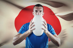 Composite image of portrait of rugby player in blue jersey holding ball Royalty Free Stock Photography