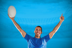 Composite image of portrait of rugby player in blue jersey holding ball with arms raised Royalty Free Stock Image