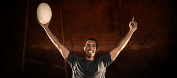 Composite image of portrait of rugby player in blue jersey holding ball with arms raised. Portrait of rugby player in blue jersey holding ball with arms raised Stock Photos