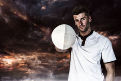 Composite image of portrait of rugby player holding the ball with one hand Stock Photo