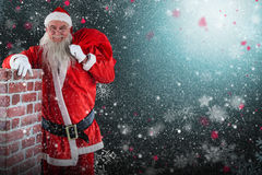 Composite image of portrait of santa claus carrying bag full of gifts by chimney. Portrait of Santa Claus carrying bag full of gifts by chimney against snowflake Royalty Free Stock Images