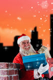 Composite image of portrait of santa claus carrying various gifts Stock Images