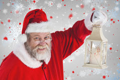 Composite image of portrait of santa claus holding christmas lantern Royalty Free Stock Photography