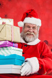 Composite image of portrait of santa claus holding stack christmas presents. Portrait of Santa Claus holding stack Christmas presents against red snow flake stock photography