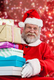 Composite image of portrait of santa claus holding stack christmas presents. Portrait of Santa Claus holding stack Christmas presents against white snow and Stock Images