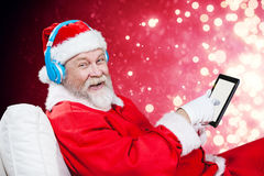 Composite image of portrait of santa claus listening music with digital tablet Stock Images