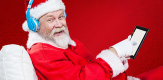 Composite image of portrait of santa claus listening music with digital tablet. Portrait of Santa Claus listening music with digital tablet  against red Stock Image