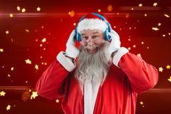 Composite image of portrait of santa claus listening to music on headphones. Portrait of Santa Claus listening to music on headphones against bright star pattern Stock Photos