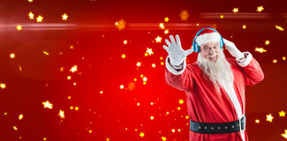 Composite image of portrait of santa claus listening to music on headphones. Portrait of Santa claus listening to music on headphones against bright star pattern Stock Photography
