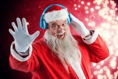 Composite image of portrait of santa claus listening to music on headphones. Portrait of Santa Claus listening to music on headphones against light design Stock Image