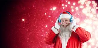 Composite image of portrait of santa claus listening to music on headphones. Portrait of Santa Claus listening to music on headphones against light design Stock Photo