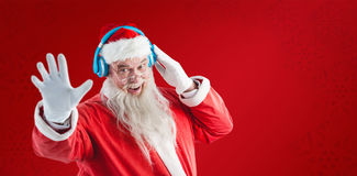 Composite image of portrait of santa claus listening to music on headphones. Portrait of Santa Claus listening to music on headphones against red snowflake Stock Images
