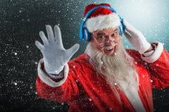 Composite image of portrait of santa claus listening to music on headphones. Portrait of Santa Claus listening to music on headphones against snowflake pattern Stock Image