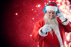 Composite image of portrait of santa claus listening to music on headphones while pointing. Portrait of Santa Claus listening to music on headphones while Stock Photography