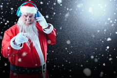 Composite image of portrait of santa claus listening to music on headphones while pointing. Portrait of Santa Claus listening to music on headphones while Stock Image