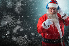 Composite image of portrait of santa claus listening to music on headphones while pointing. Portrait of Santa Claus listening to music on headphones while Stock Photo