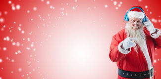 Composite image of portrait of santa claus listening to music on headphones while pointing. Portrait of Santa Claus listening to music on headphones while Stock Images