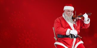 Composite image of portrait of santa claus playing violin Stock Image