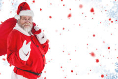 Composite image of portrait of santa claus pointing while carrying christmas bag Stock Photography