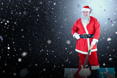 Composite image of portrait of santa claus standing with guitar and gift boxes Stock Photography