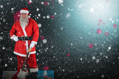 Composite image of portrait of santa claus standing with guitar and gift boxes Stock Photos