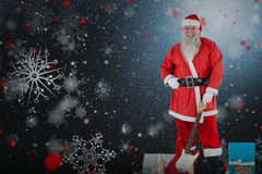 Composite image of portrait santa claus standing with guitar and gifts Royalty Free Stock Images