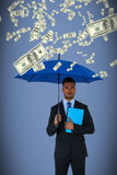 Composite image of portrait of serious businessman holding blue umbrella and file. Portrait of serious businessman holding blue umbrella and file  against grey Royalty Free Stock Photo