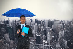 Composite image of portrait of serious businessman holding blue umbrella and file. Portrait of serious businessman holding blue umbrella and file  against high Stock Photos